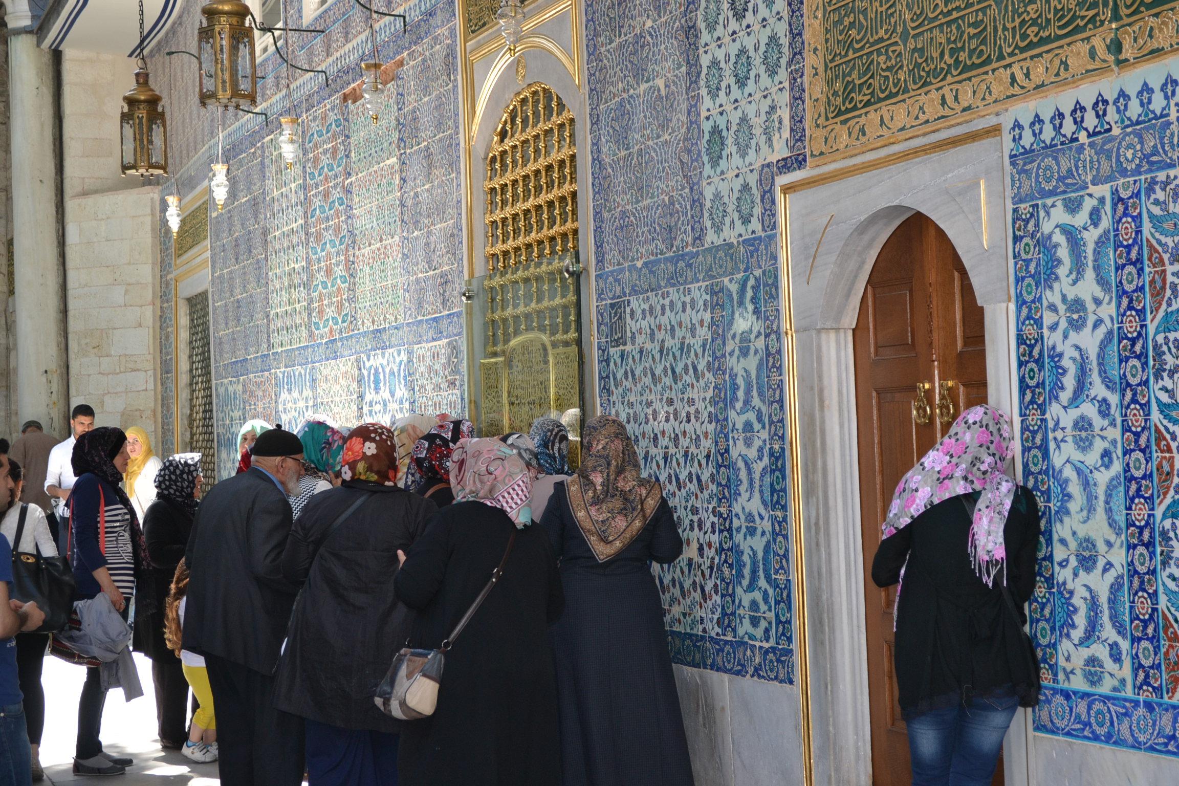Vierailijoita rukoilemassa hautakammion seinän vieressä