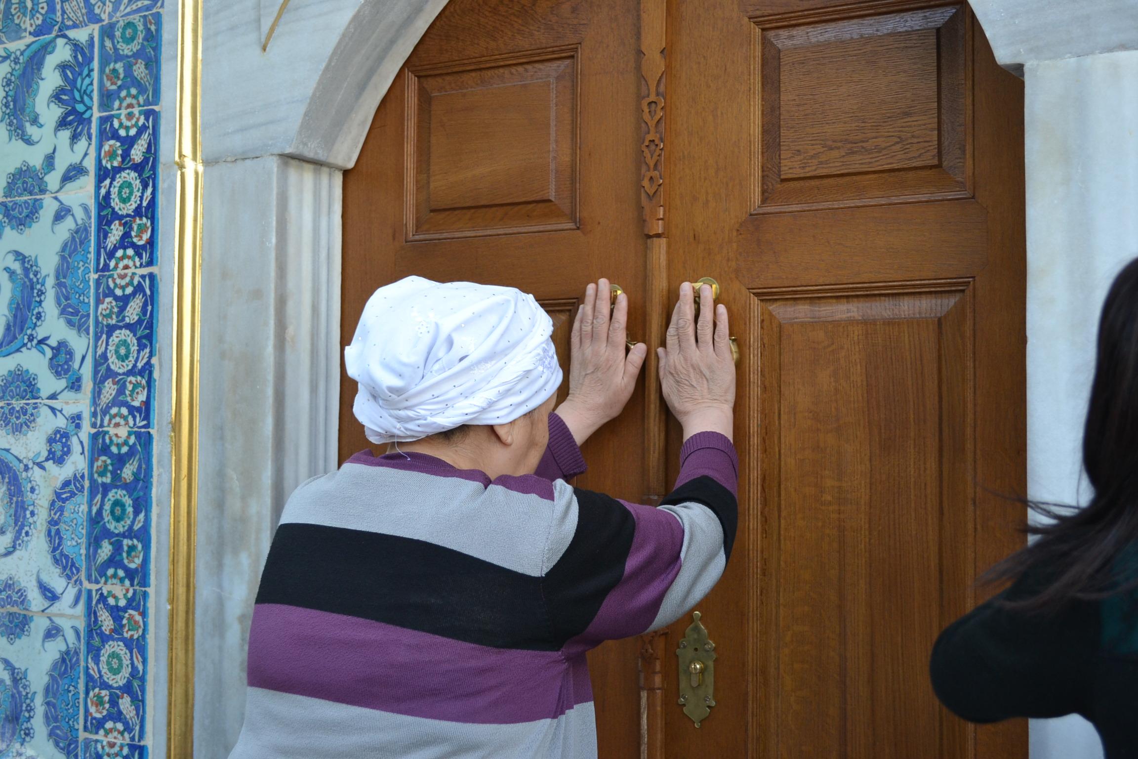 Vanha nainen silittää hautakammion ovea rukouksen yhteydessä