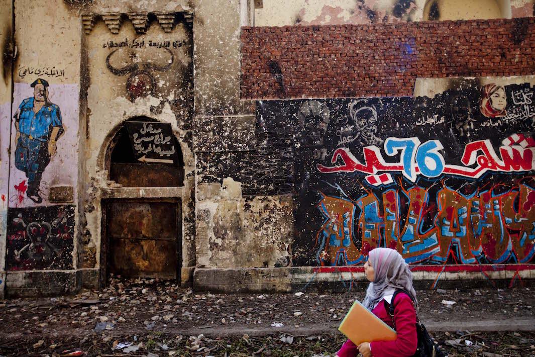 Huivipäinen nainen ja osittain murentunut ja katutaidetta täynnä oleva seinä