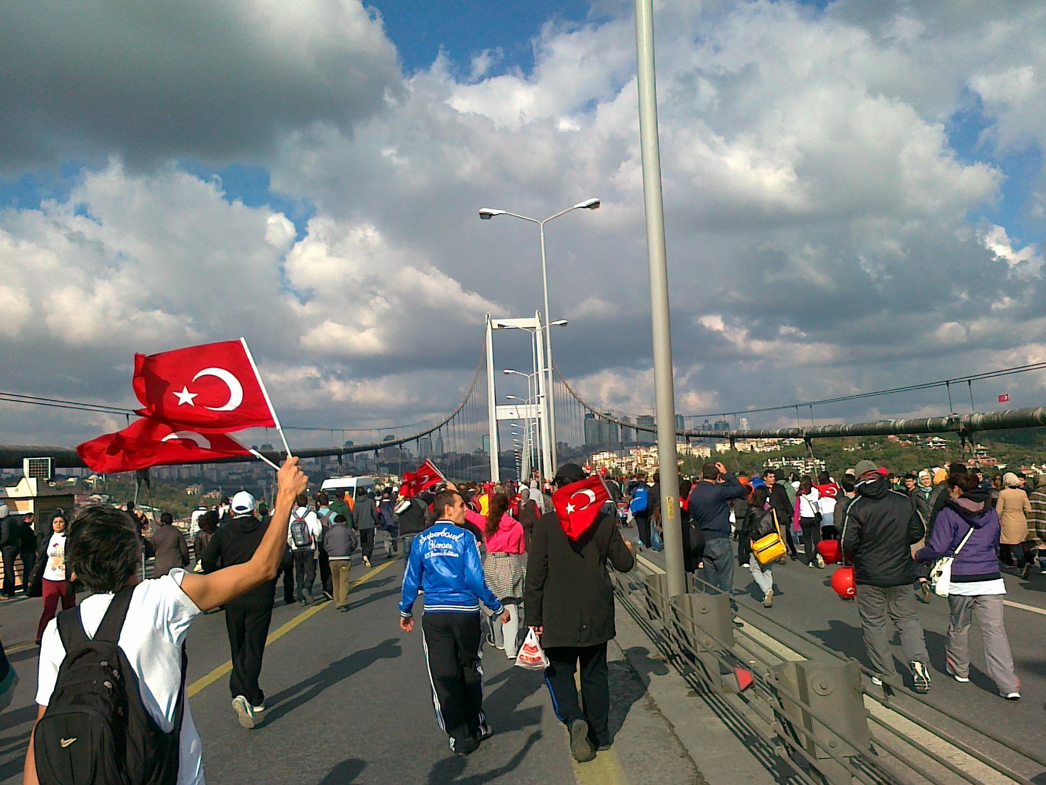 kuvituskuva, ihmiset sillalla Turkin lippujen kanssa