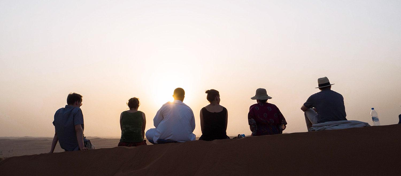 Kuvituskuva, ihmiset istumassa dyynillä auringonlaskussa
