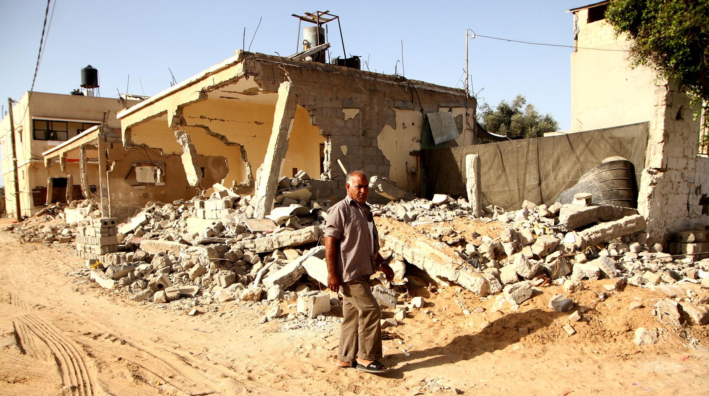 Mies kävelee talon raunioiden edessä Gazassa