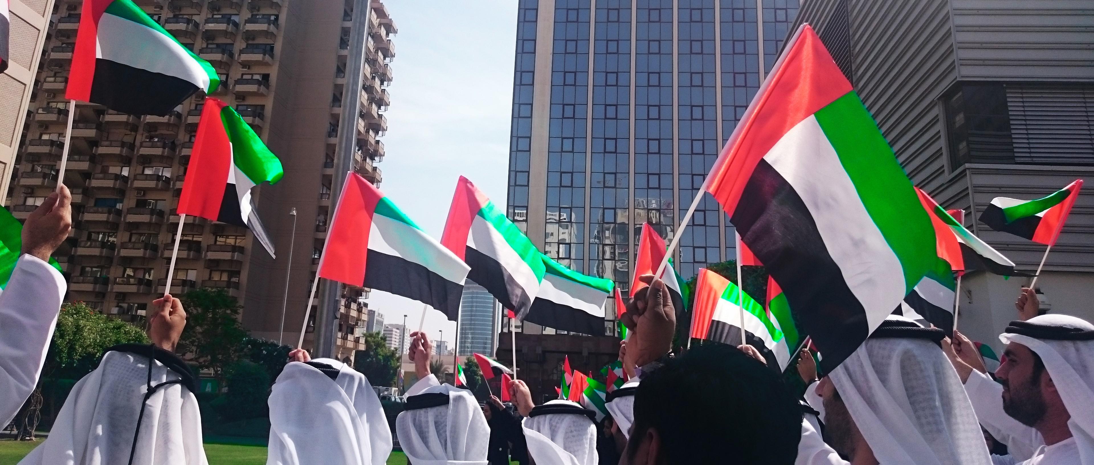 Ihmiset heiluttavat Emiraattien lippuja