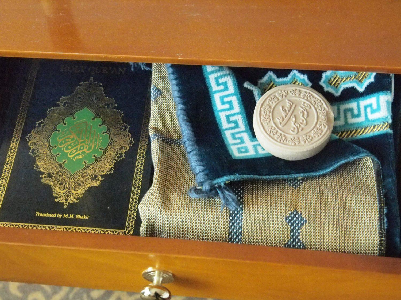 Koraani, rukousmatto ja savikiekko piirongin laatikossa