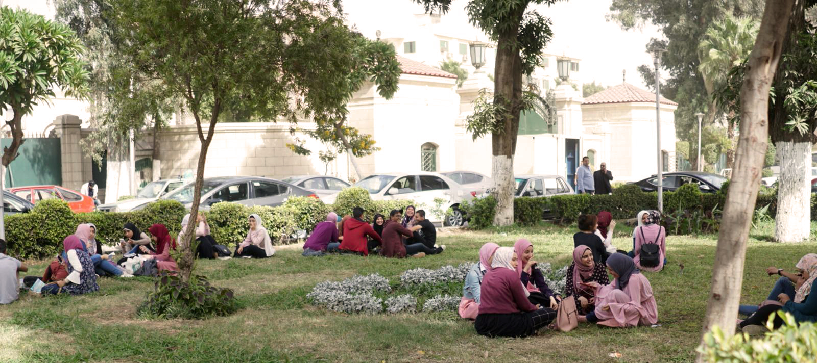 Hunnutettuja naisia istumassa nurmikolla puistossa