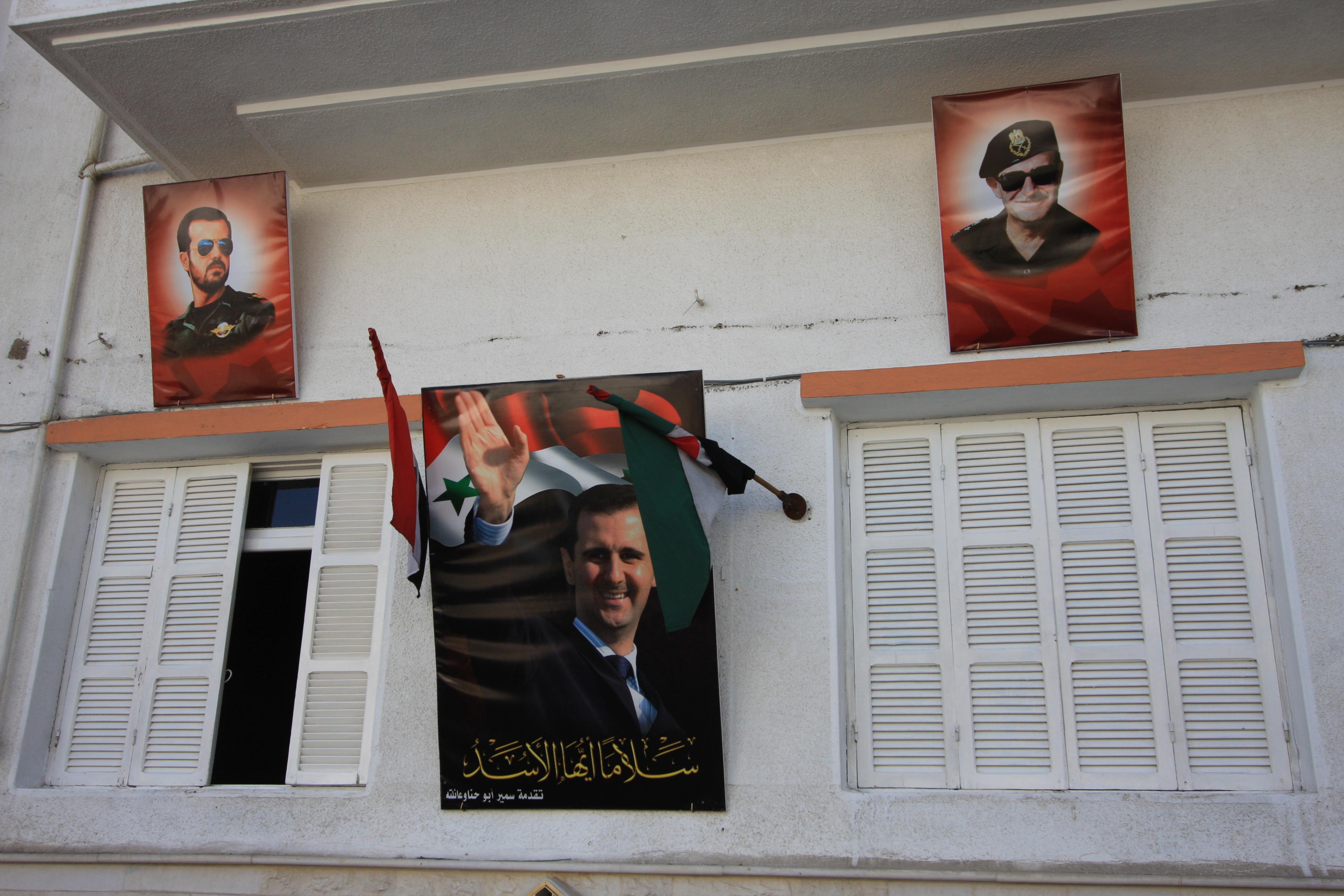 Assadin juliste ja Syyrian liput talon ulkoseinällä