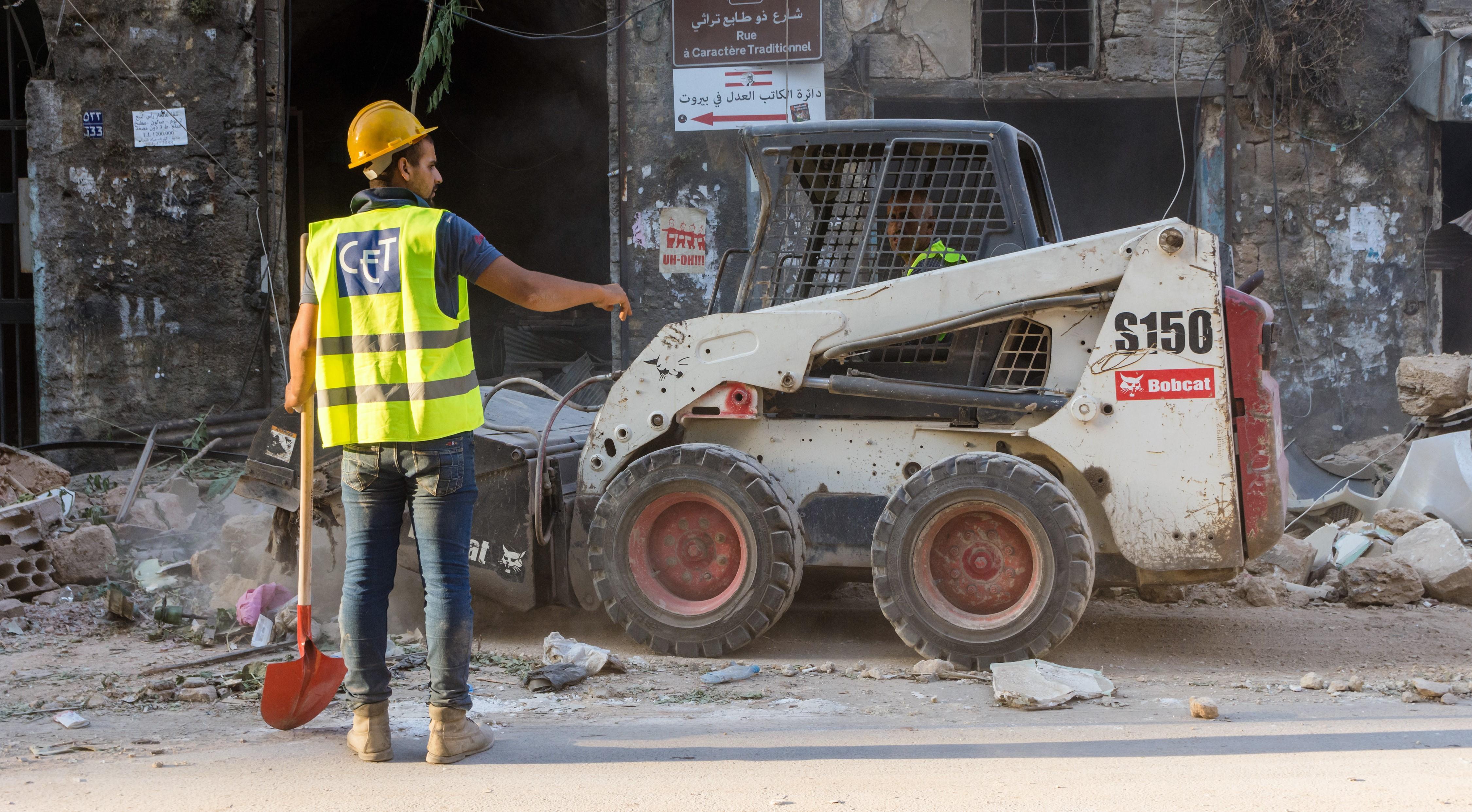 työmies siivoamassa räjähdyksen jälkiä