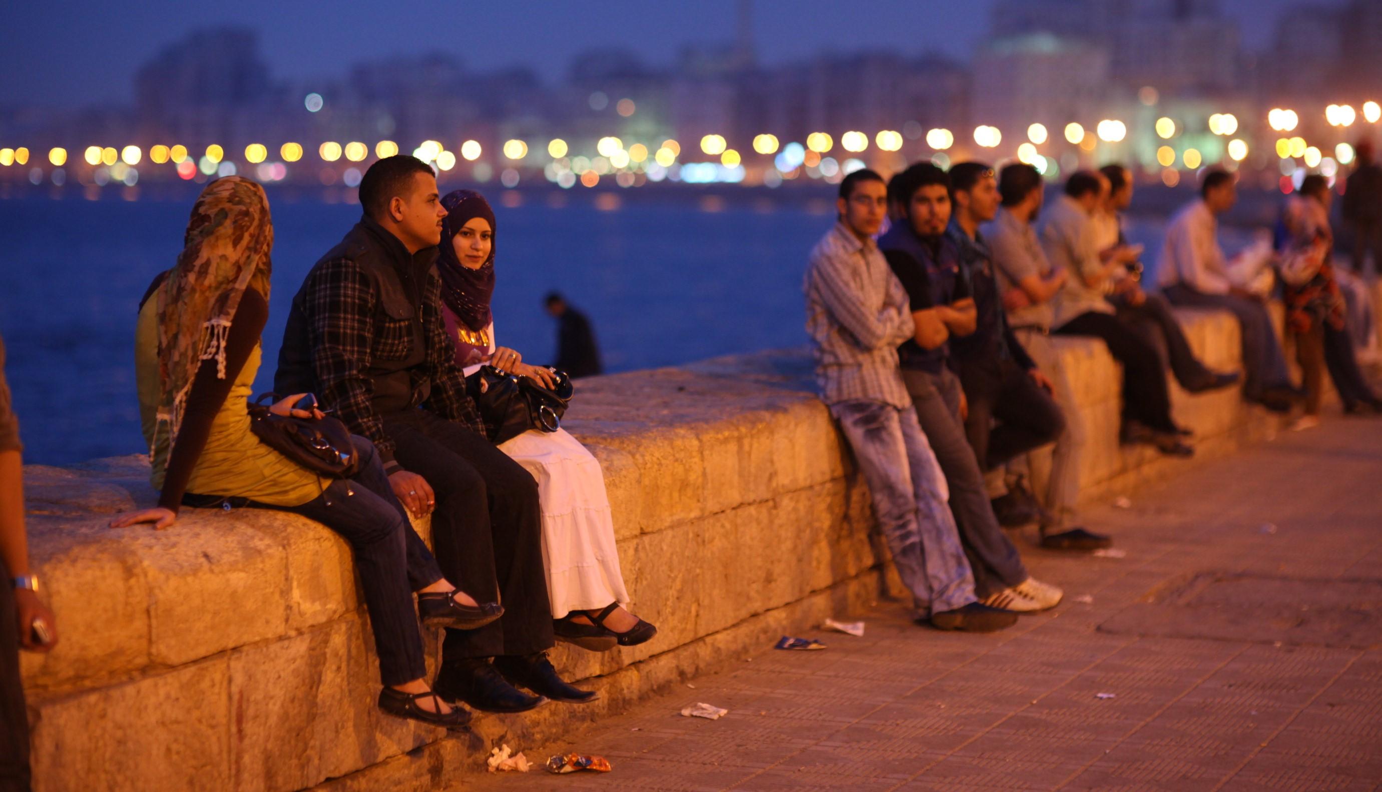 Egyptiläisiä nuoria istumassa kävelykadun vieressä