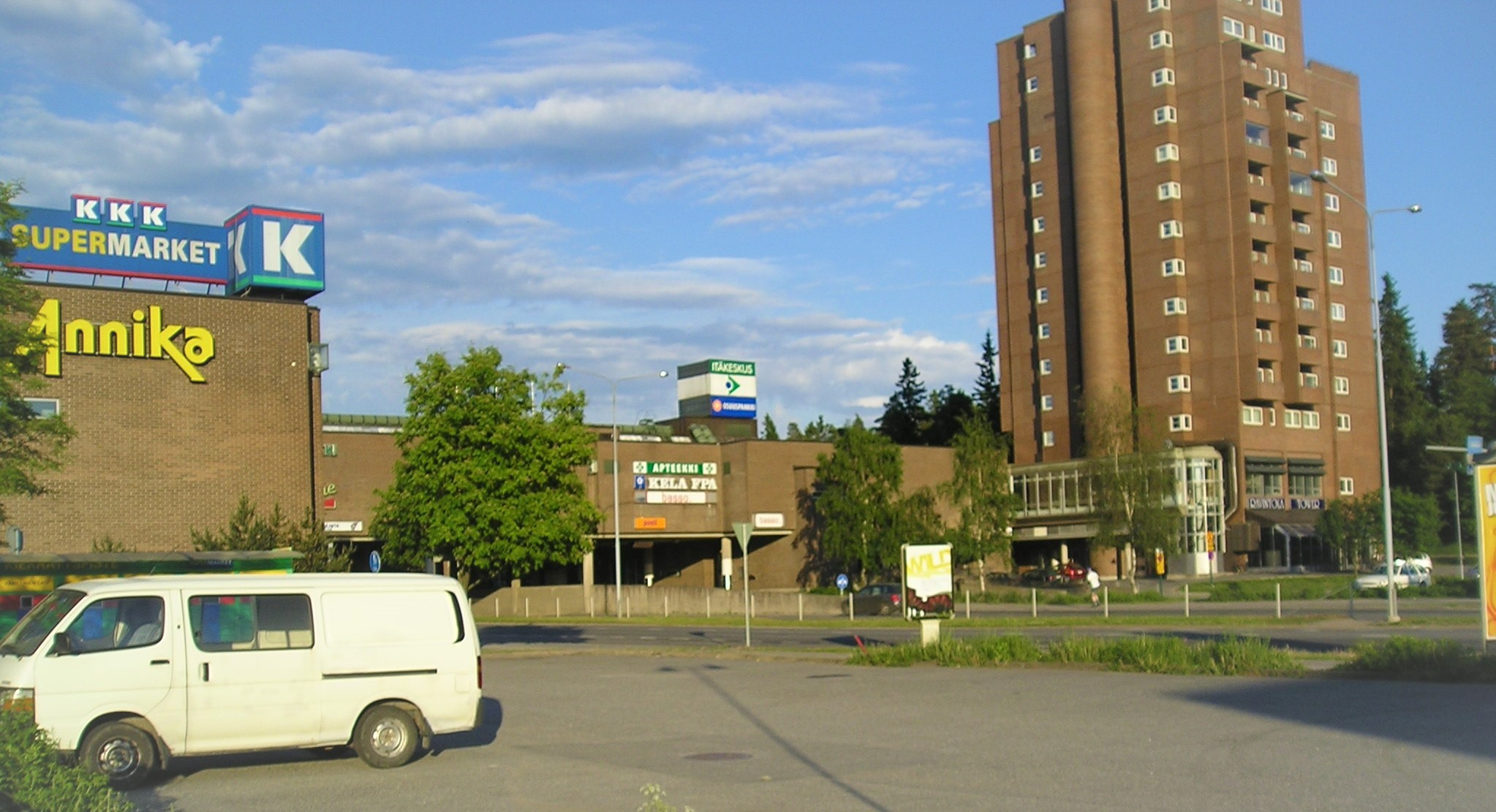 Näkymä vanhan kauppakeskuksen parkkipaikalle, jossa parkkeerattuna on vaalea pakettiauto. Kauppakeskuksessa näkyy isolla K-supermarketin ja Kelan logot. Vieressä on ruskeasta tiilistä rakennettu kerrostalo.