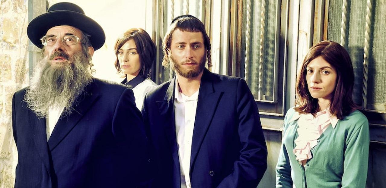Kaksi naista ja kaksi miestä ortodoksijuutalaisissa vaatteissa seisoo ja katsoo kohden katsojaa.