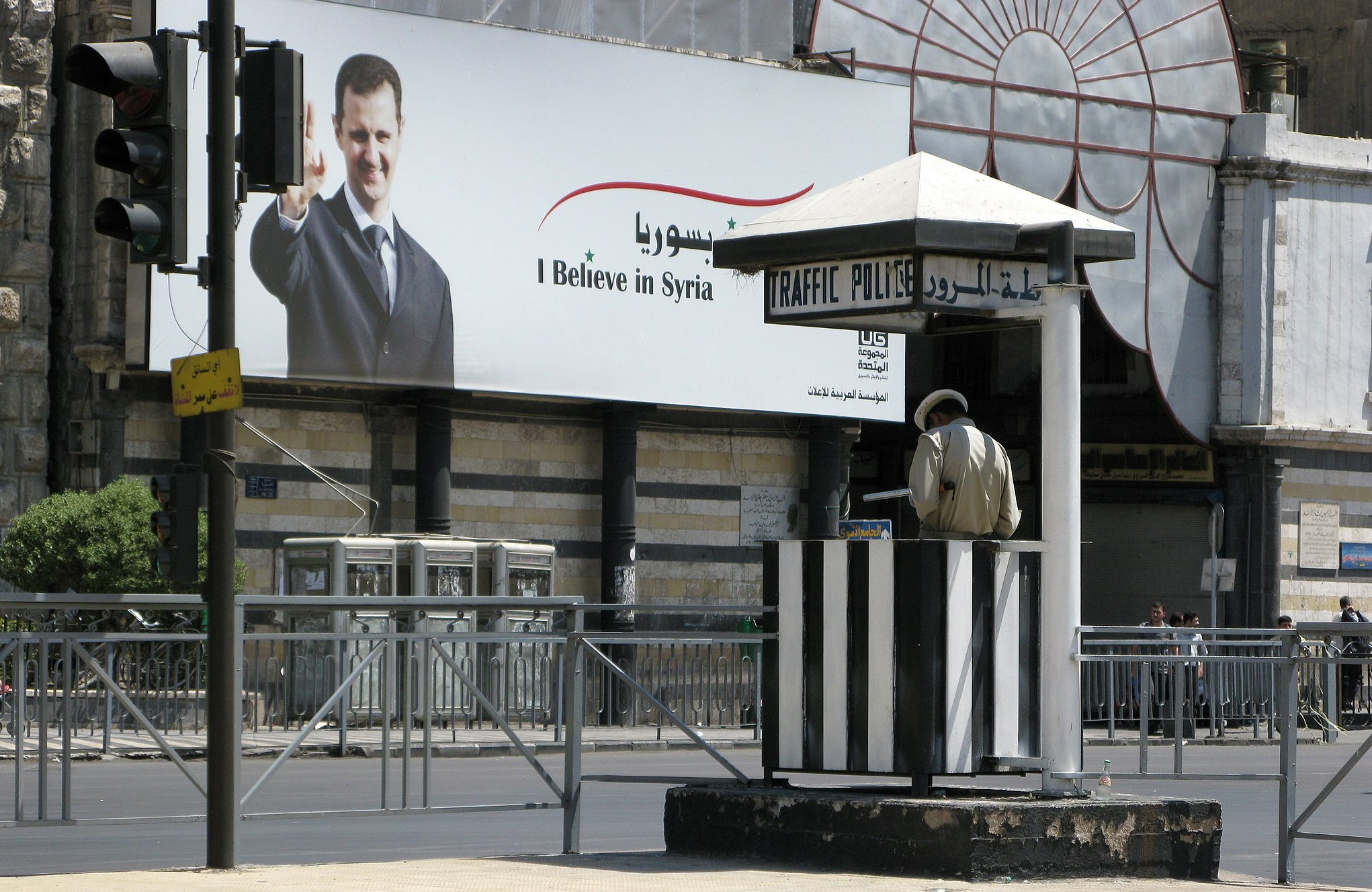 """A poster of Assad with text """"I believe in Syria""""."""