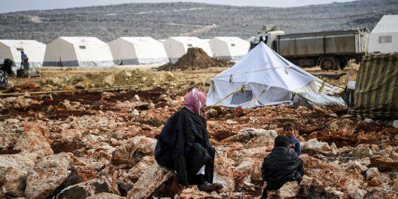 2 lasta ja mies palestiinalaishuivi päässä istuvat kivikossa. Taustalla on pakolaistelttoja, säiliöauto ja kukkula