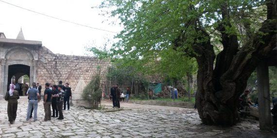 Ryhmö miehiä seisoo jesiditemppelin edustalla olevalla aukiolla. Oikeassa laidassa iso puu.