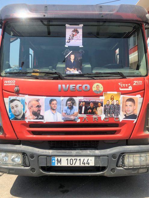 Kuvassa paloauto, jonka etuosa on koristeltu ihmisten kuvilla.