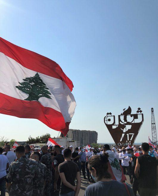 Libanonin lippu liehuu väkijoukossa, taustalla arabiankielinen monumentti ja varastorakennus.