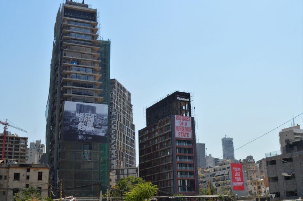 Kuvassa kaksi korkeaa rakennusta, joiden seinässä isot julisteet.