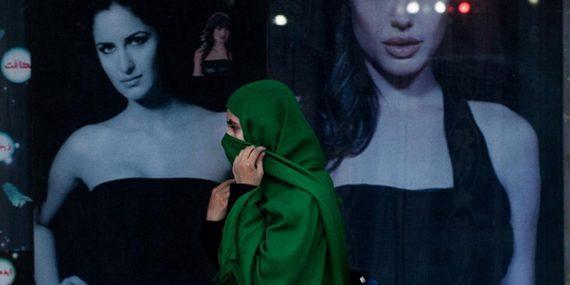 Vihreään huiviin kääriytynyt nainen kävelee kauneussalongin ohi, jonka seinässä on kaksi suurta kuvaa hunnuttumista ja avoimiin vaatteisiin pukeutuneista naisista.