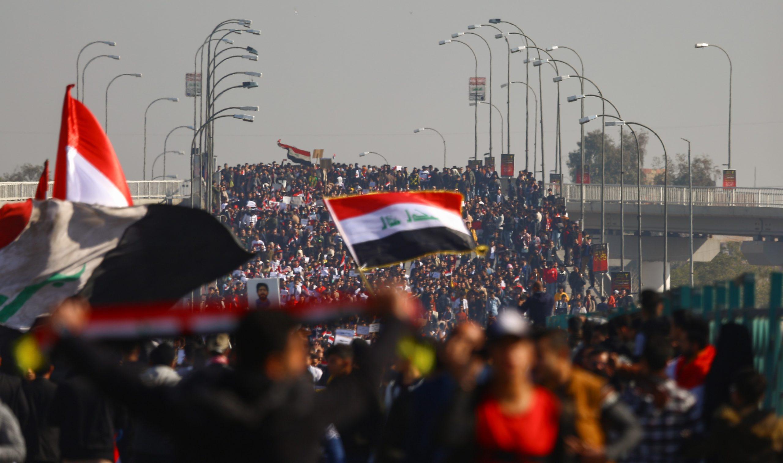 Valtava joukko irakilaisnuoria osoittaa mieltään sillalla. Irakin lippu kuvan etualalla.