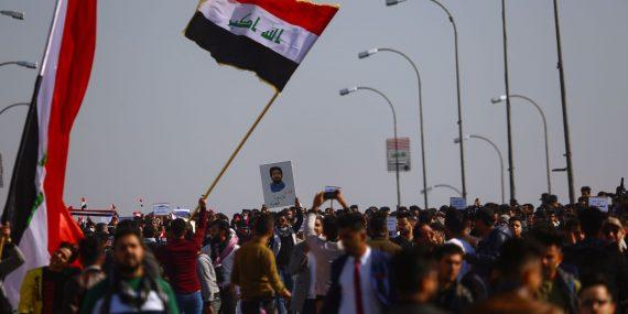 Suuri joukko irakilaisnuoria osoittaa mieltään kadulla. He heiluttavat Irakin lippuja ja pitävät käsissään kylttejä.